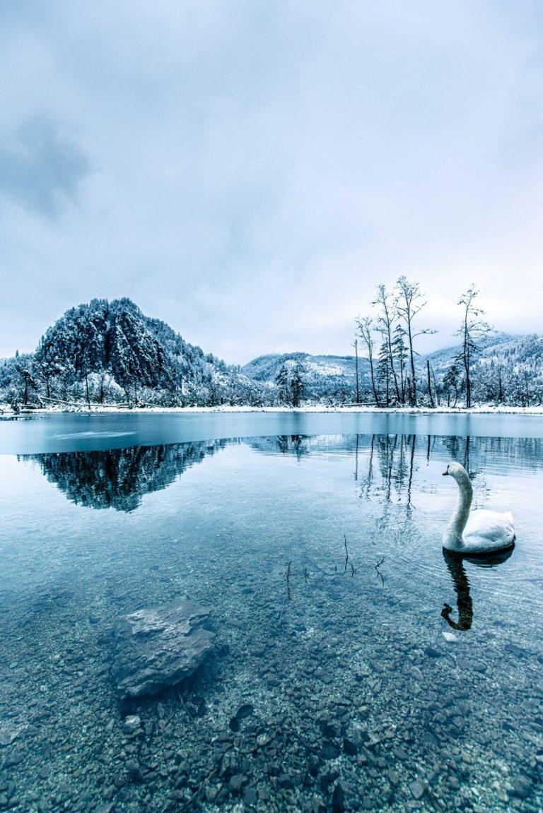 Eine Bergspitze reflektiert sich in einem halb gefrorenem See.