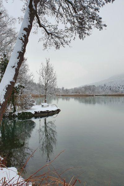 Ein verschneiter Tag am See, überall liegt Schnee: auf der Parkbank und auf allen umstehenden Bäumen.