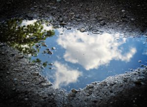 Pfütze in der sich Wolken spiegeln